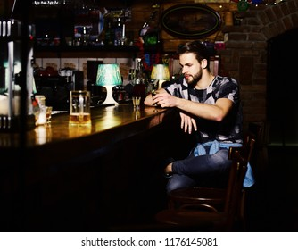 Guy sits at bar counter with glasses of shot and liqueur. Man with beard drinks alcohol on blurred bar background. Macho has rest in bar and drinks shot or liqueur. Alcohol and party concept.