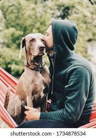 un mec est assis avec un chien sur un hamac et l'embrasse