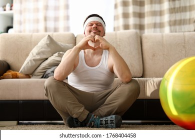 Guy sits at home carpet meditates and shows heart. Get out your usual comfort zone. Relaxing therapy improves your workout productivity. Cope with emotional pressure in stressful situations - Shutterstock ID 1768404458