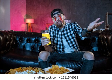 The guy sits on the couch drinking beer from painted glass and pours drawn tears out of his eyes. Crazy surreal art collage