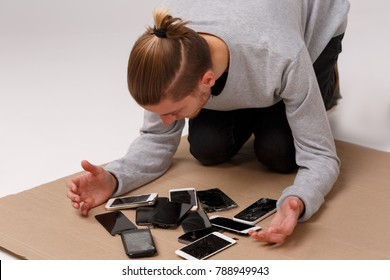 A guy sits on his knees bending over a pile of different shattered and broken smartphones.