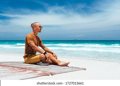 guy sits on the shore of a tropical beach. A panoramic view of the sea  with a sandy beach, on a clear summer day, a blue sky with white clouds. Amazing landscape. Copy place