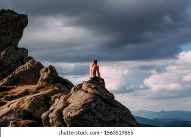 A guy sits on a stone in the mountains and looks into the distance. Rest after a difficult climb