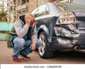 Guy sitting near the wrecked car after the accident, clutching his head.