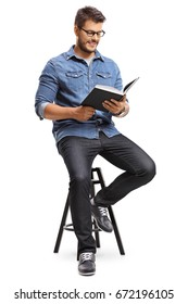 Guy sitting on a chair and reading a book isolated on white background