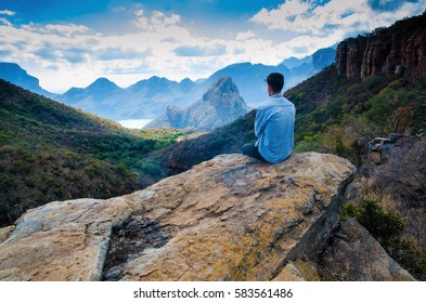 A guy sitting on a rock and looking at the view of Blyde River Canyon, Mpumalanga, Republic South Africa.