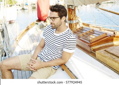 Guy sitting onboard boat, looking away