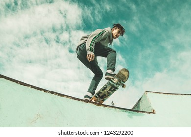 Guy skateboarder riding a skateboard on a skatepark. A young man jumping with a skateboard