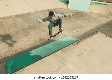 Guy skateboarding and doing tricks in a skatepark. Skateboarder jumping