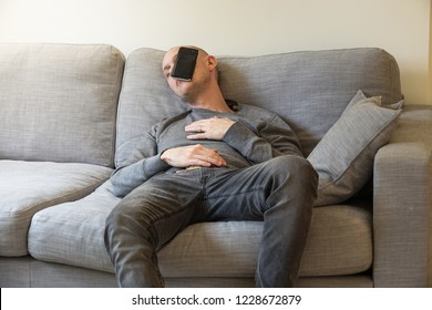 A guy is sleeping on a couch with a smartphone on his face.