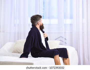 Guy sleepy looking at window in morning. Awakening concept. Macho with beard and mustache sluggish relaxing after nap, rest. Man in robe sits on bed, white curtains on background.