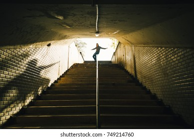 Guy sliding of the railing in an old tunnel in the city. Youth concept.