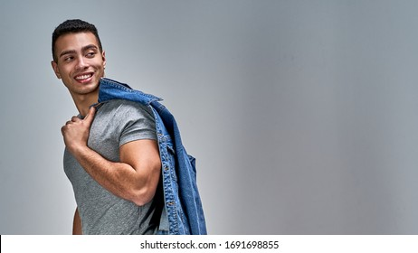 Guy with smile with bristles with athletic build looking back over his shoulder.