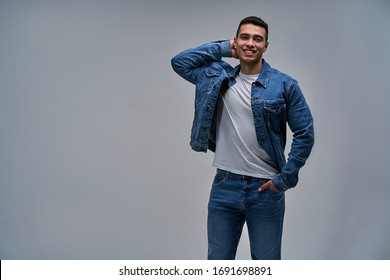 Guy with smile with bristles with athletic build with hand on the nape looking at the camera.