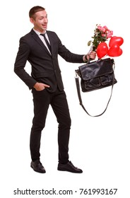 A guy with a smile holds a bouquet and a bag with balls on a white isolated background