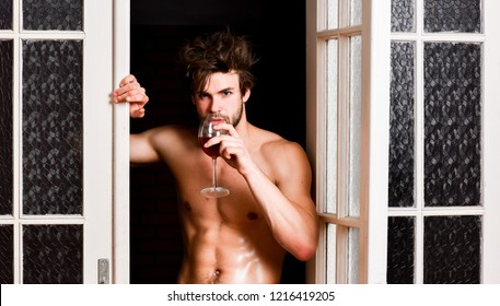 Guy smooth skin posing seductive. Beginning great evening. Man with sexy torso drink wine. Bachelor sexy body. Sexy attractive macho tousled hair coming out through bedroom door. Sexy lover concept.