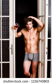 Guy smooth skin posing seductive. Beginning great evening. Man with sexy torso drink wine. Sexy attractive macho tousled hair coming out through bedroom door. Bachelor sexy body. Sexy lover concept.