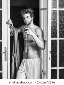 Guy smooth skin wear bathrobe. Beginning of great evening. Bachelor sexy body. Sexy attractive macho tousled hair coming out through bedroom door. Man with sexy torso drink wine. Sexy lover concept.
