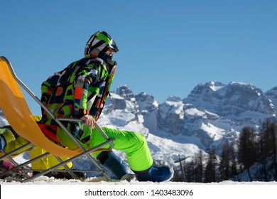 The guy the snowboarder sits on a chaise lounge on a ski slope.