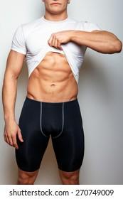 Guy in spoertswear showing his muscular stomach