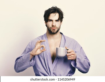 Guy or sportsman in home or bath clothes drinks tea or coffee. Sexy macho in bathrobe with mug showing perfect sign. Morning concept. Man with beard in blue dressing gown on grey background.