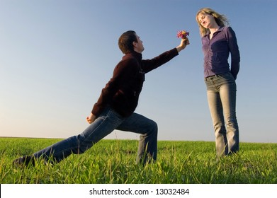 Guy stand on a knee and gives a bouquet to the girl