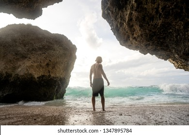 guy standing in the cave with a view of the waves of the ocean
