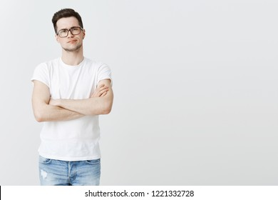 Guy standing with displeased look disliking, making negative opinion about show. Disappointed young attractive man with bristle in glasses crossing hands on chest and smirking from dissatisfaction