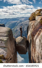 A guy standing on the famous boulder (Kjeragbolten) stuck between two rocks above a fjord. Popular hiking destination near Lysebotn, Rogaland, Norway.