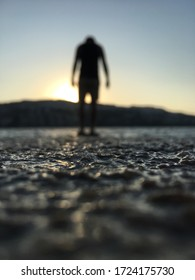 A guy stands with his head bowed on the seashore, seeing off the sunset.  Sun dips below the horizon.