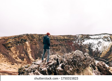 The guy stands on a rock above Lake Kerid - a crater volcanic lake in Iceland. Red volcanic soil, similar to Martian landscapes. He enjoys the view from the mountain.