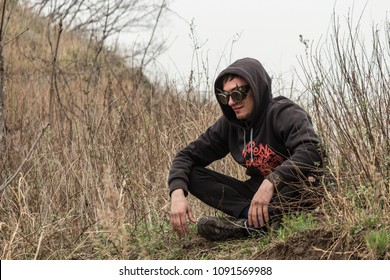 A guy in Steampunk goggles and a hood sits in a lotus position among the tall dry grass
