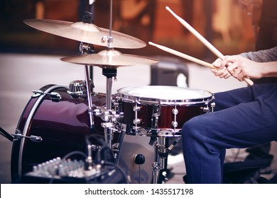 Guy is a street musician in blue pants playing rhythm on a beautiful red drum set with wooden drumsticks