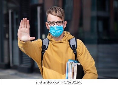 Guy Student, Schüler Junge, junger Mann in Schutzmaske und Brille auf der offenen Universität mit Büchern, Schulbücher zeigen Handfläche, Hand, stoppen kein Zeichen. Virus, pandemisches Koronavirus-Konzept. Covid-19