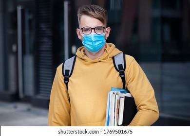 Guy Student, Schüler Junge, junger Mann in Schutzmaske und Brille auf der Außenuniversität mit Büchern, Lehrbücher sehen Kamera. Virus, pandemisches Koronavirus-Konzept. Covid-19, Sicherheitsstudie