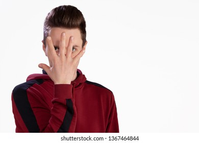 The guy in the studio on a white background posing covering his face with his hand.