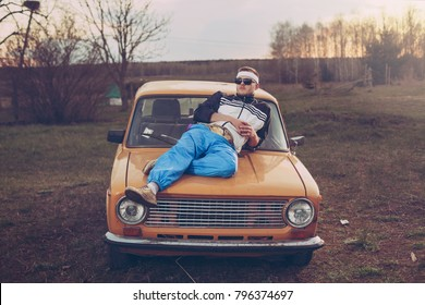 guy in the style of the 90s lies on the hood of an old car