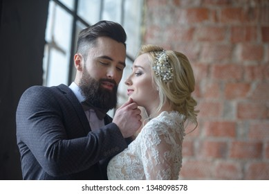 The guy in the suit with the beard and the girl in the dress of the bride