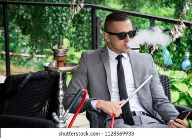 Guy in suit and black tie smoking hookah outside