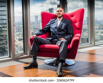 guy in a suit in an expensive office with panoramic windows