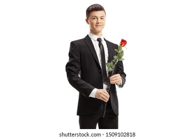 Guy in a suit holding a red rose and smiling at the camera isolated on white background