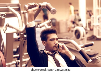 The guy in the suit and white shirt in the gym, talking on the phone and performs the exercise