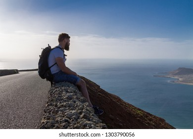 A guy in summer clothes is sitting on a stone fence and looks at a nearby island in the ocean.