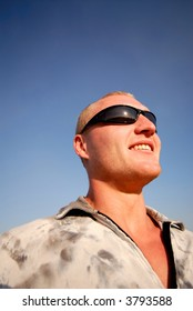 guy in sunglasses smiles on  background of  dark blue sky