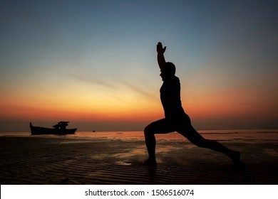 guy at sunset on the island practices yoga, silhouette