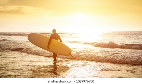 Guy surfer walking with surfboard at sunset in Tenerife - Surf long board training practitioner in action - Sport travel concept with sof focus water near feet - Warm sunshine color foltered tones