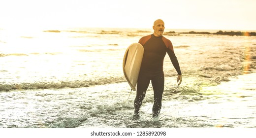 Guy surfer walking with surfboard at sunset in Tenerife - Surf long board training practitioner in action - Sport travel concept with soft focus due to backlight - Warm sunshine color filtered tones