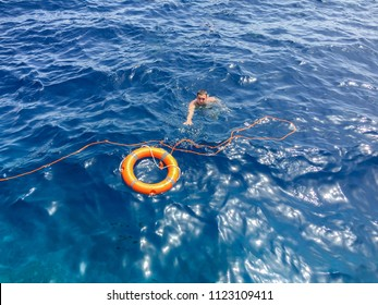 The guy is swimming in the sea with a lifebuoy. Salvation of man with the help of a lifebuoy. Salvation of a drowning man. Lifebuoy. Help in the water