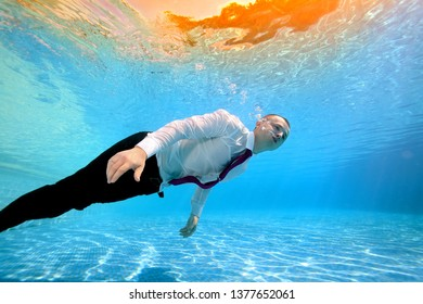 The guy is swimming underwater in the pool in a white shirt and red tie and blowing bubbles against the yellow light on the surface of the water. Conceptual photo. Bottom view. Shooting underwater