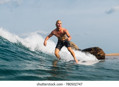 the guy swims on the surf on the wave